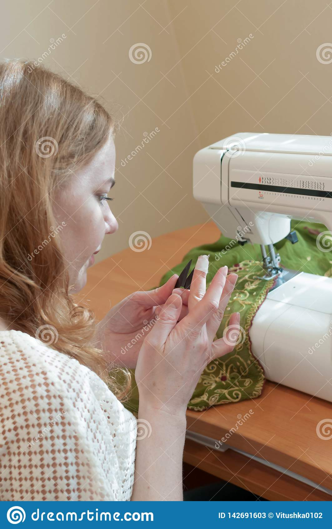 Cucitrice che si siede alla tavola con la macchina per cucire e che esamina dito ferito