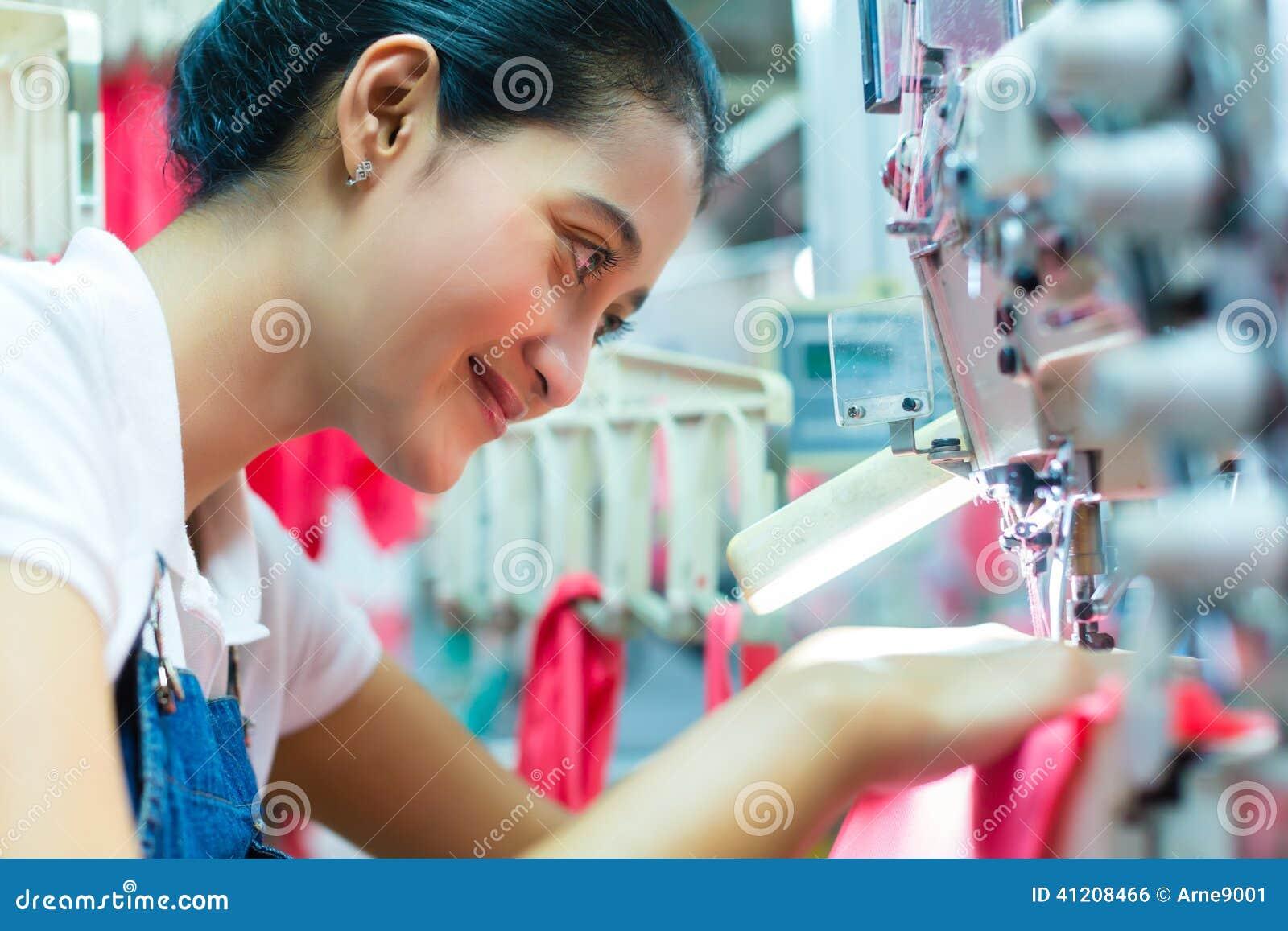 Cucitrice indonesiana nella fabbrica asiatica del tessuto
