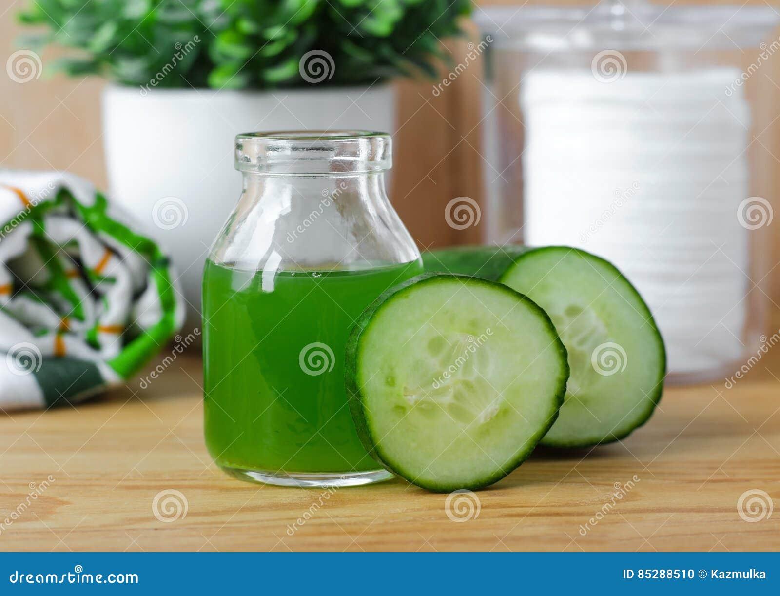 Cucumber juice in a small glass jar for preparing natural facial toner. Homemade cosmetics.