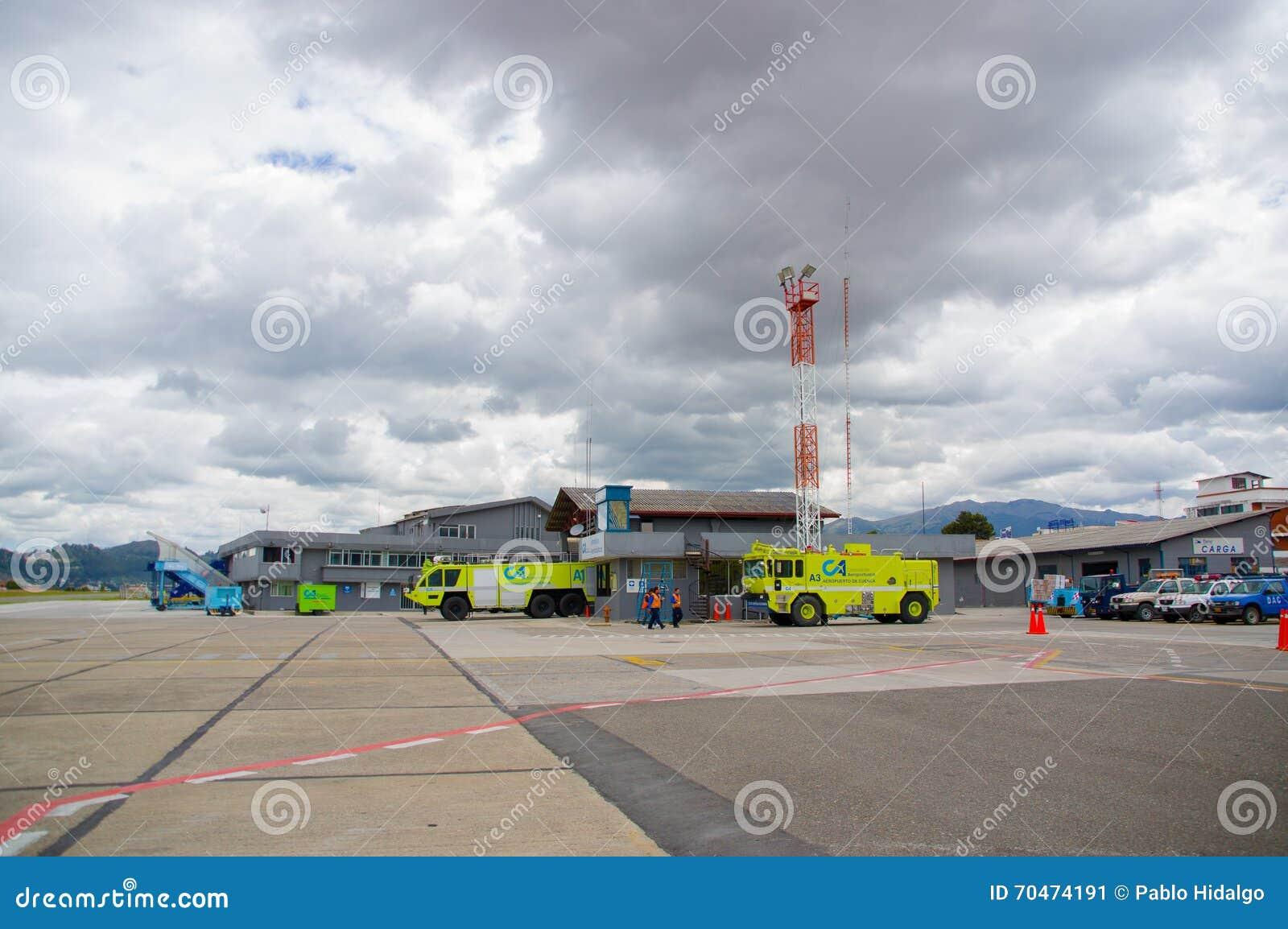 Cuenca, эквадор - 22-ое апреля 2015: Brights желтеет пожарные машины готовя рядом с взлётно-посадочная дорожка на авиапорте