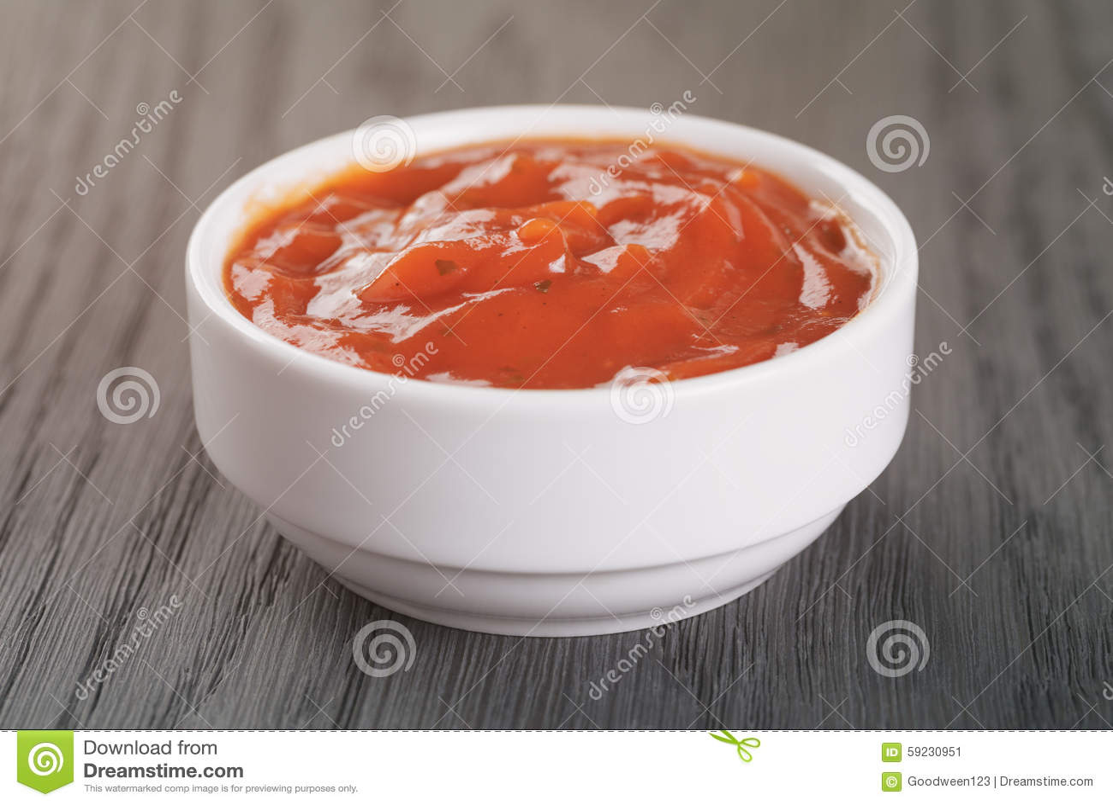 Cuenco blanco con la salsa de tomate en la tabla de madera