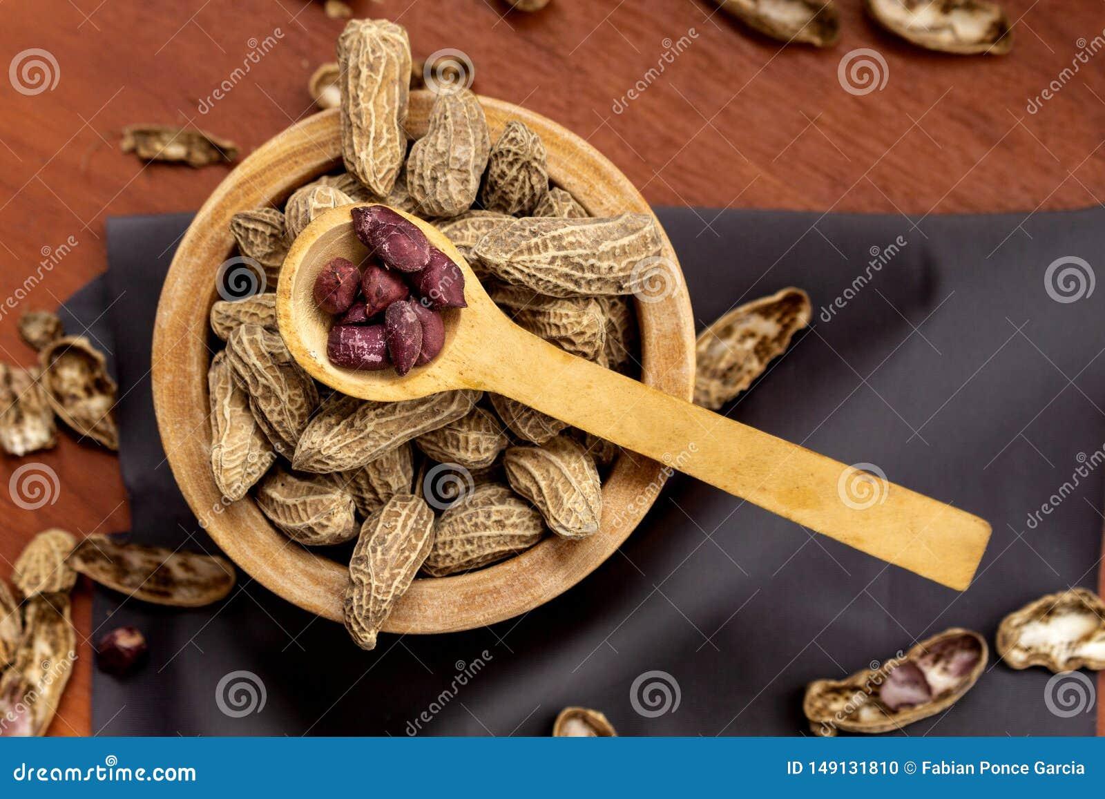 Cuenco con los cacahuetes con la c?scara y pelados con una cuchara en una superficie de madera