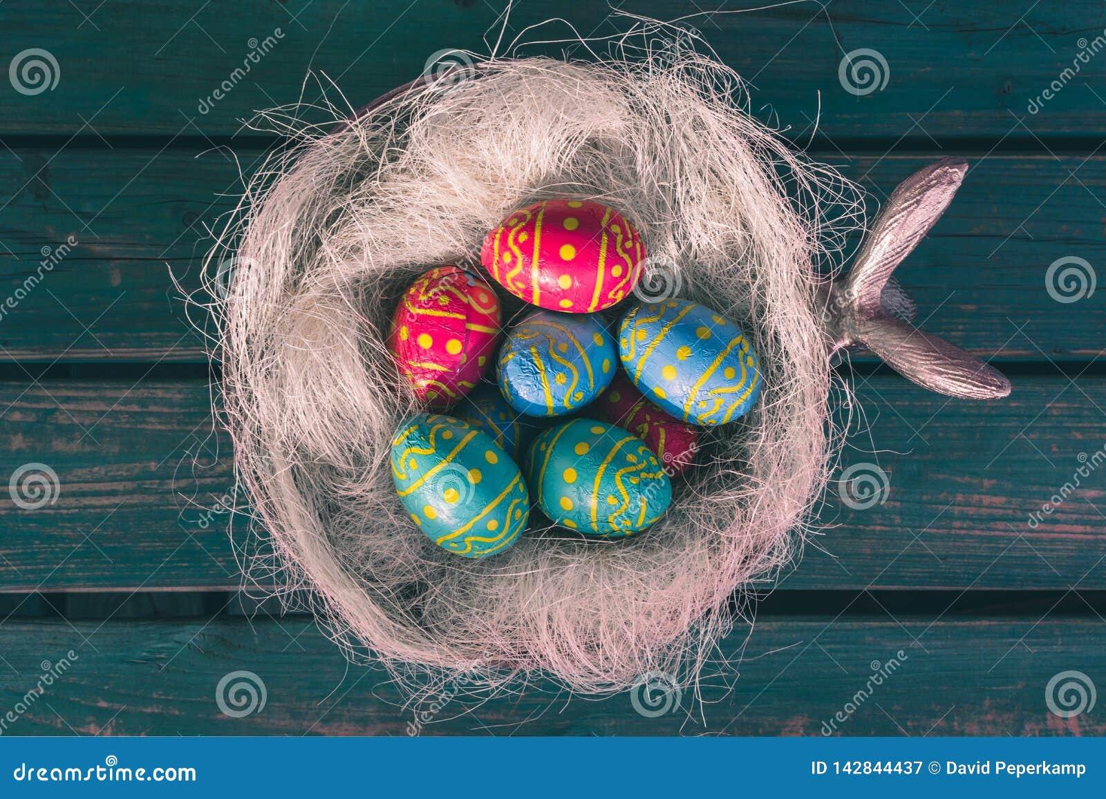 Cuenco con los huevos del choclate, banco verde, Paasdecoratie, eitjes de Pascua de los paas