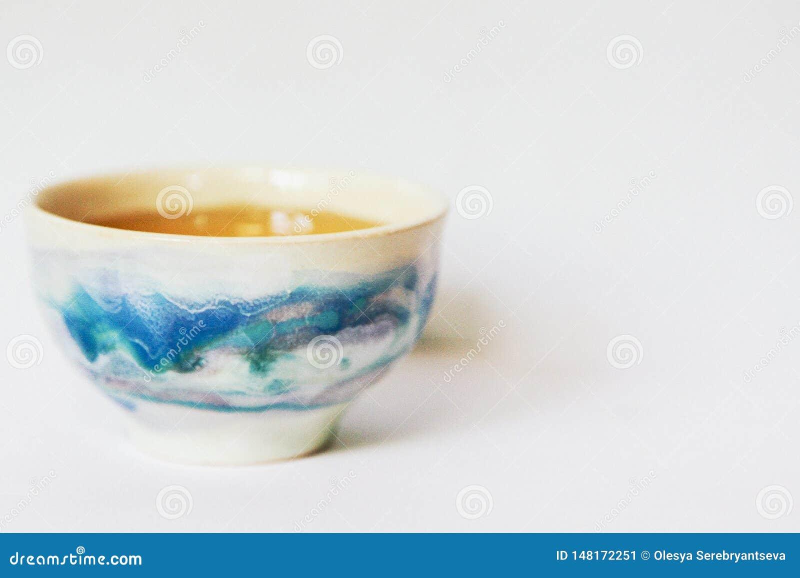 Cuenco de consumición de cerámica con té en un fondo blanco aislado Cuenco japonés con un modelo hermoso