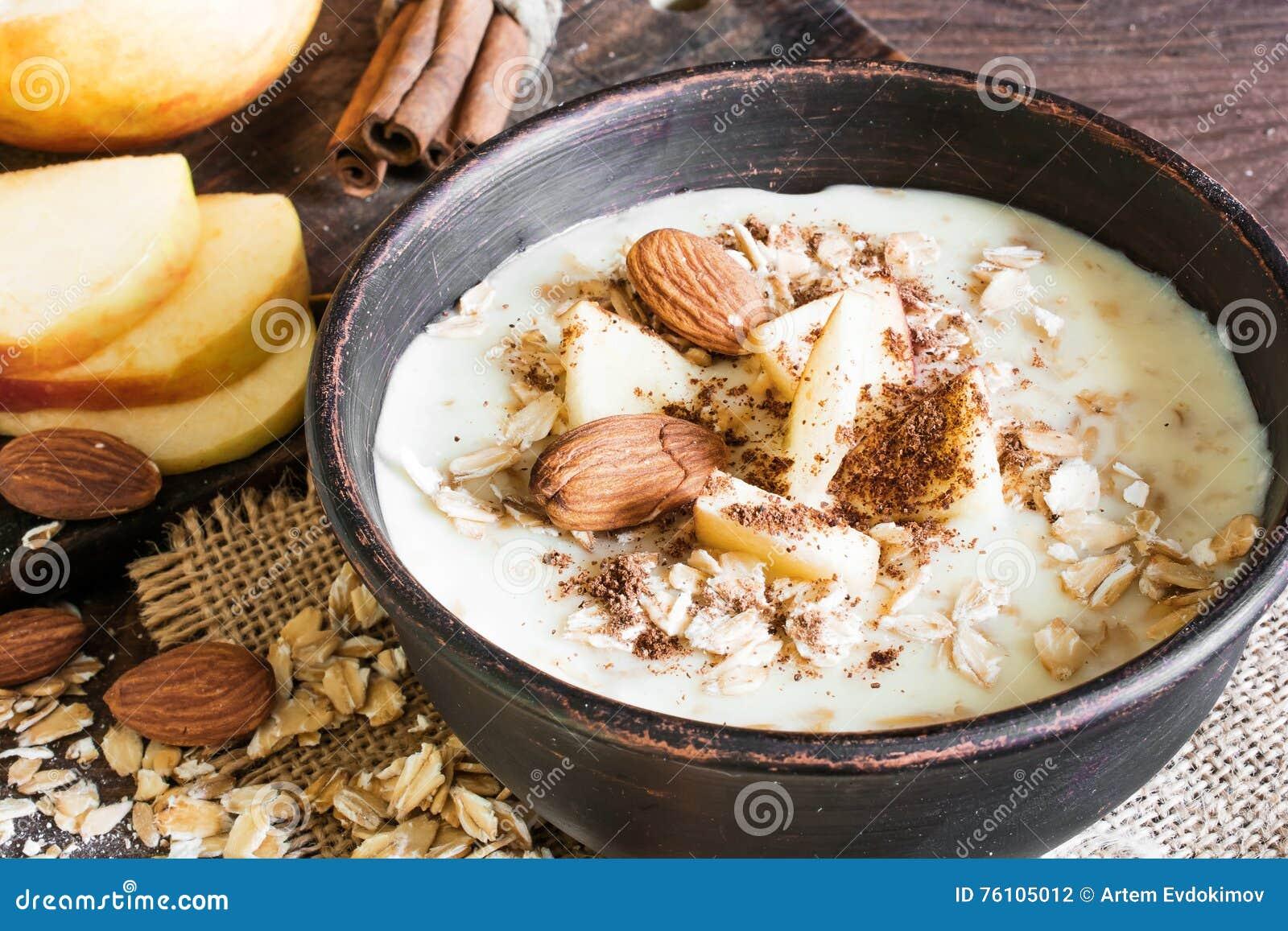 Cuenco de gachas de avena de la harina de avena con la manzana, el canela y almendras