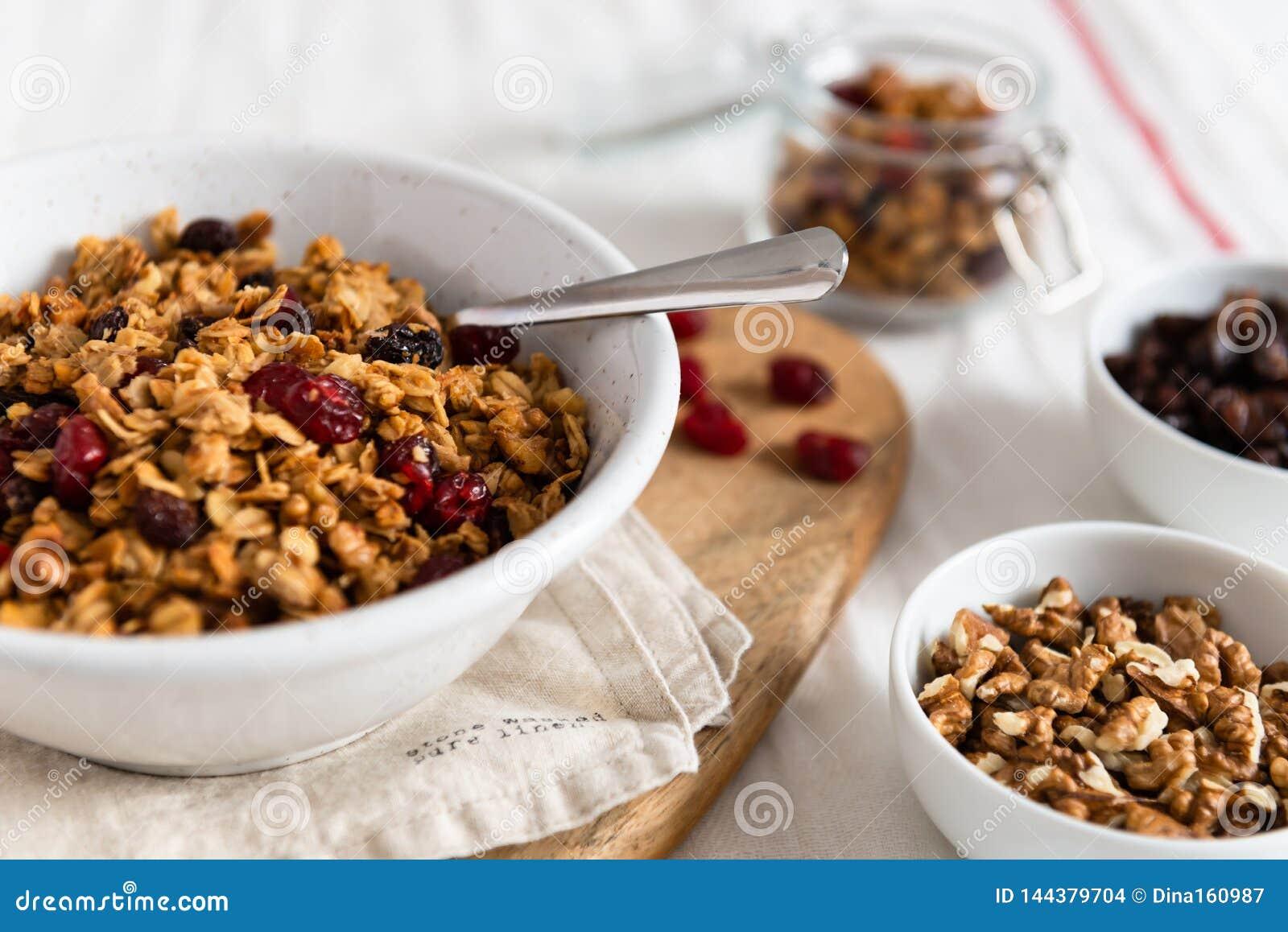 Cuenco de granola hecho en casa con las nueces y las frutas en el fondo de lino blanco Vista lateral, espacio de la copia concept