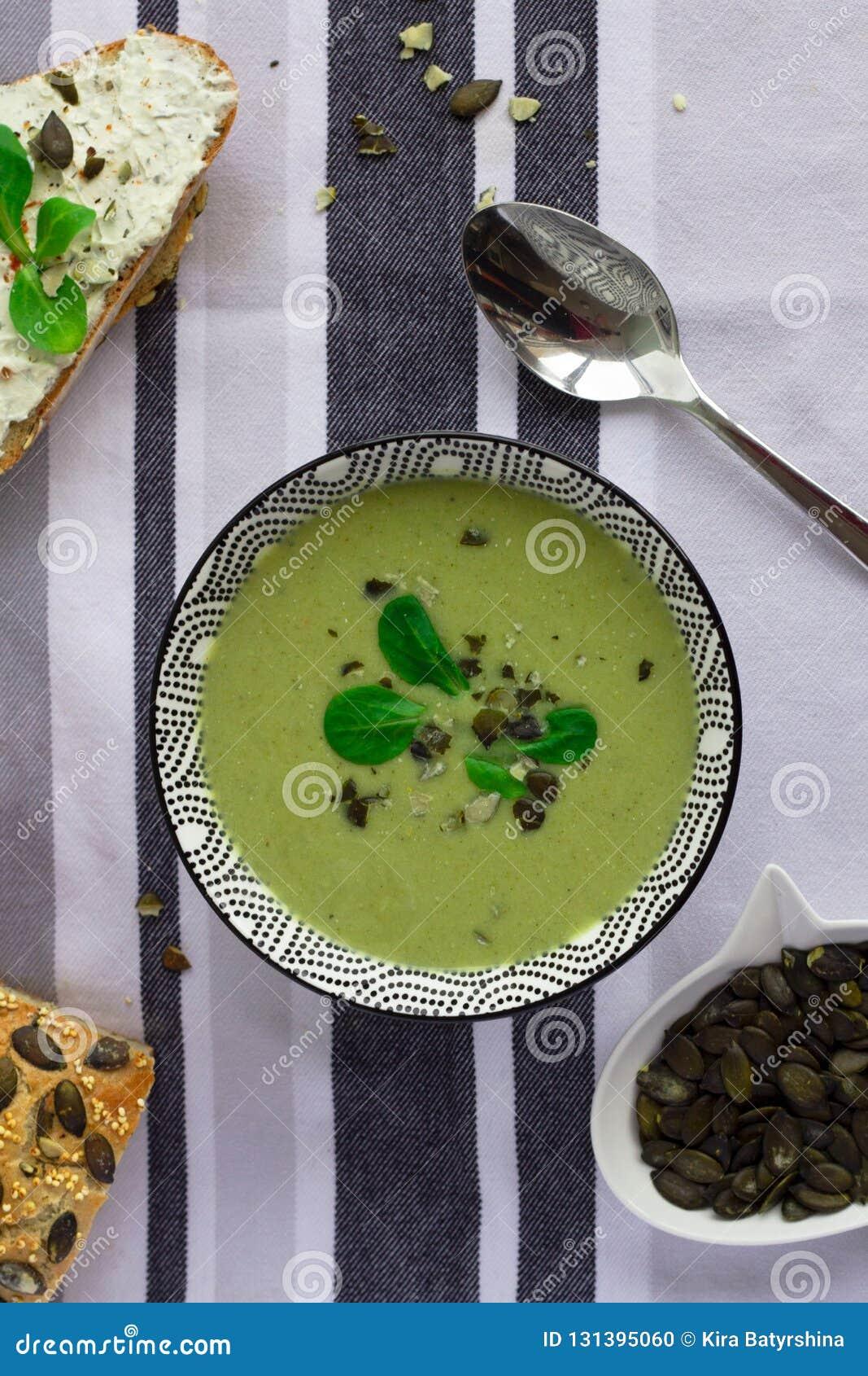 Cuenco de sopa de la crema del bróculi, de pan del grano con las semillas de calabaza y de cuchara en la tabla, concepto vegetari