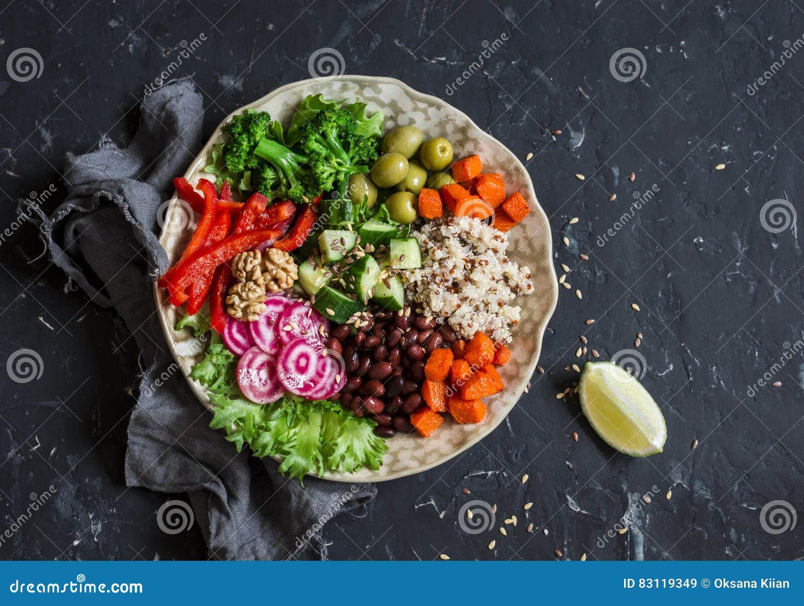 Cuenco vegetariano de la comida Quinoa, habas, patatas dulces, bróculi, pimientas, aceitunas, pepino, nueces - almuerzo sano En l