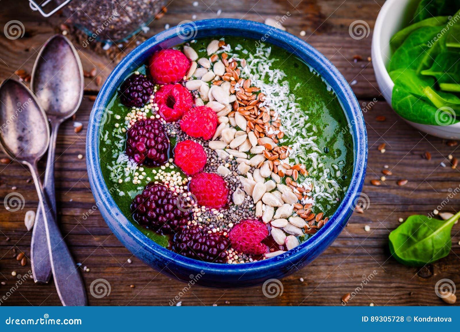 Cuenco verde del smoothie de la espinaca con la frambuesa, la zarzamora, las semillas de lino, las semillas de girasol y los micr