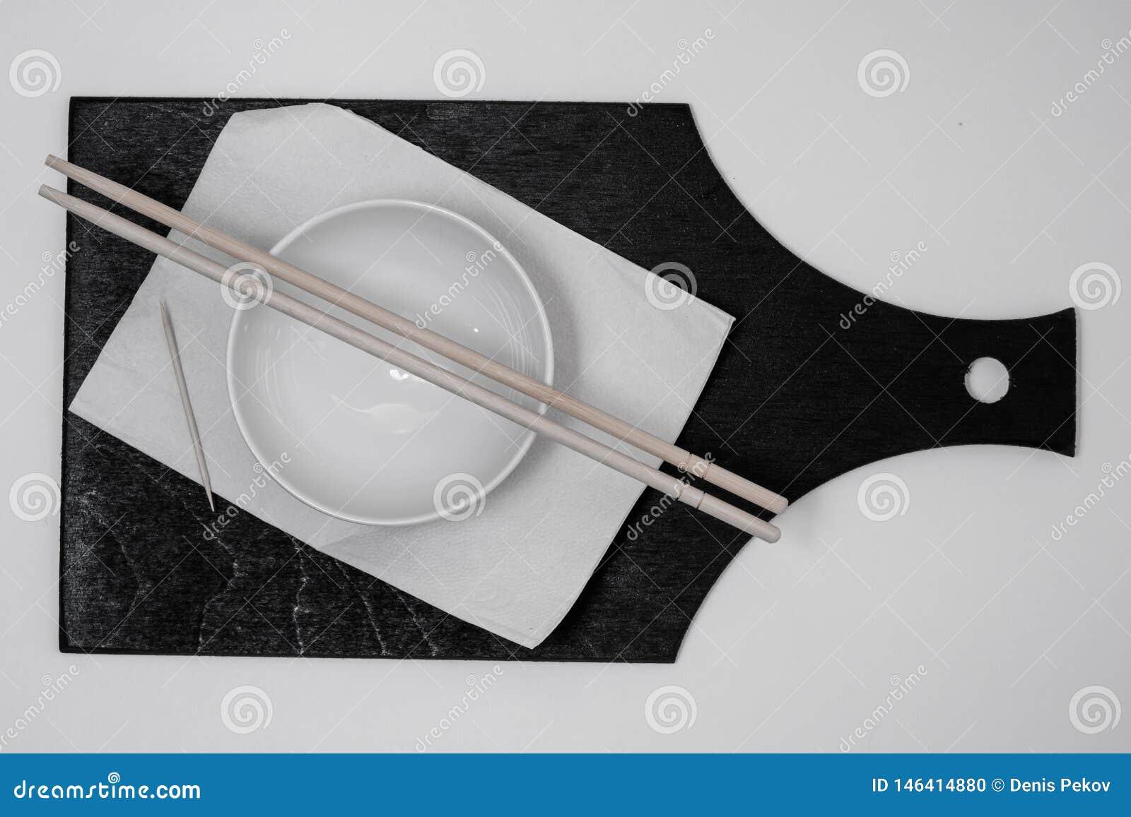 Cuenco y servilleta blancos, palillo, palillos en tablero negro
