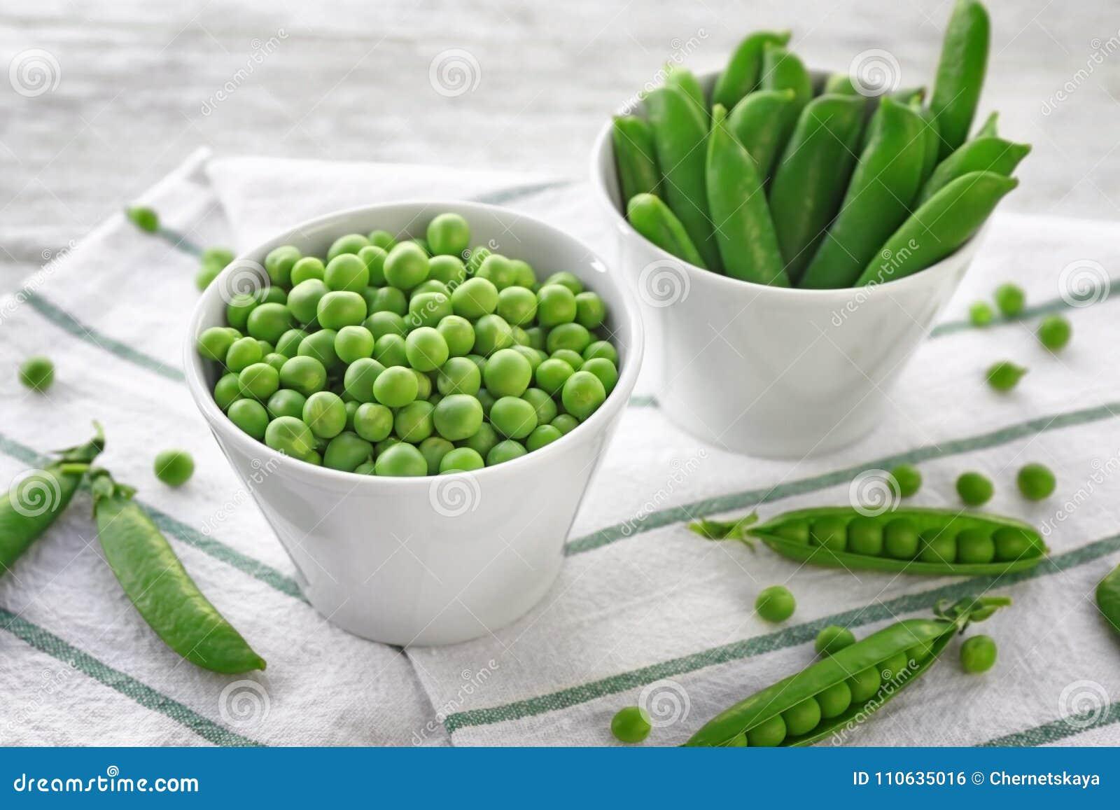 Cuencos con los guisantes verdes frescos