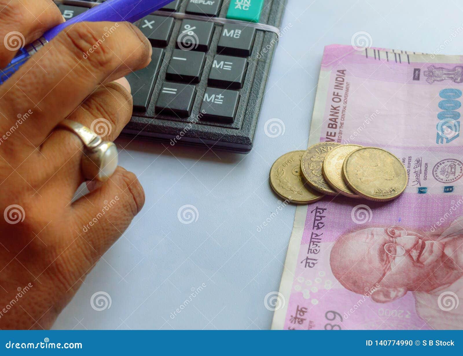 Cuenta corriente de la mujer con la calculadora y sostener una pluma con las monedas indias de las notas de la moneda Mujer de la