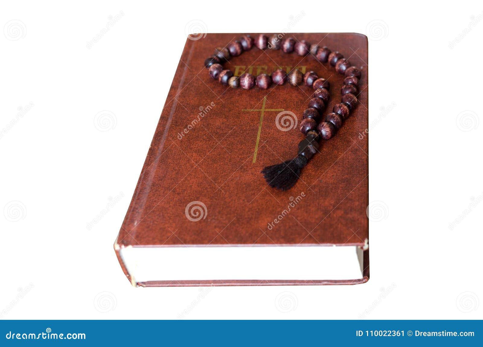 Cuerda aislada del rezo Cuerda de madera del rezo con la biblia aislada en el fondo blanco