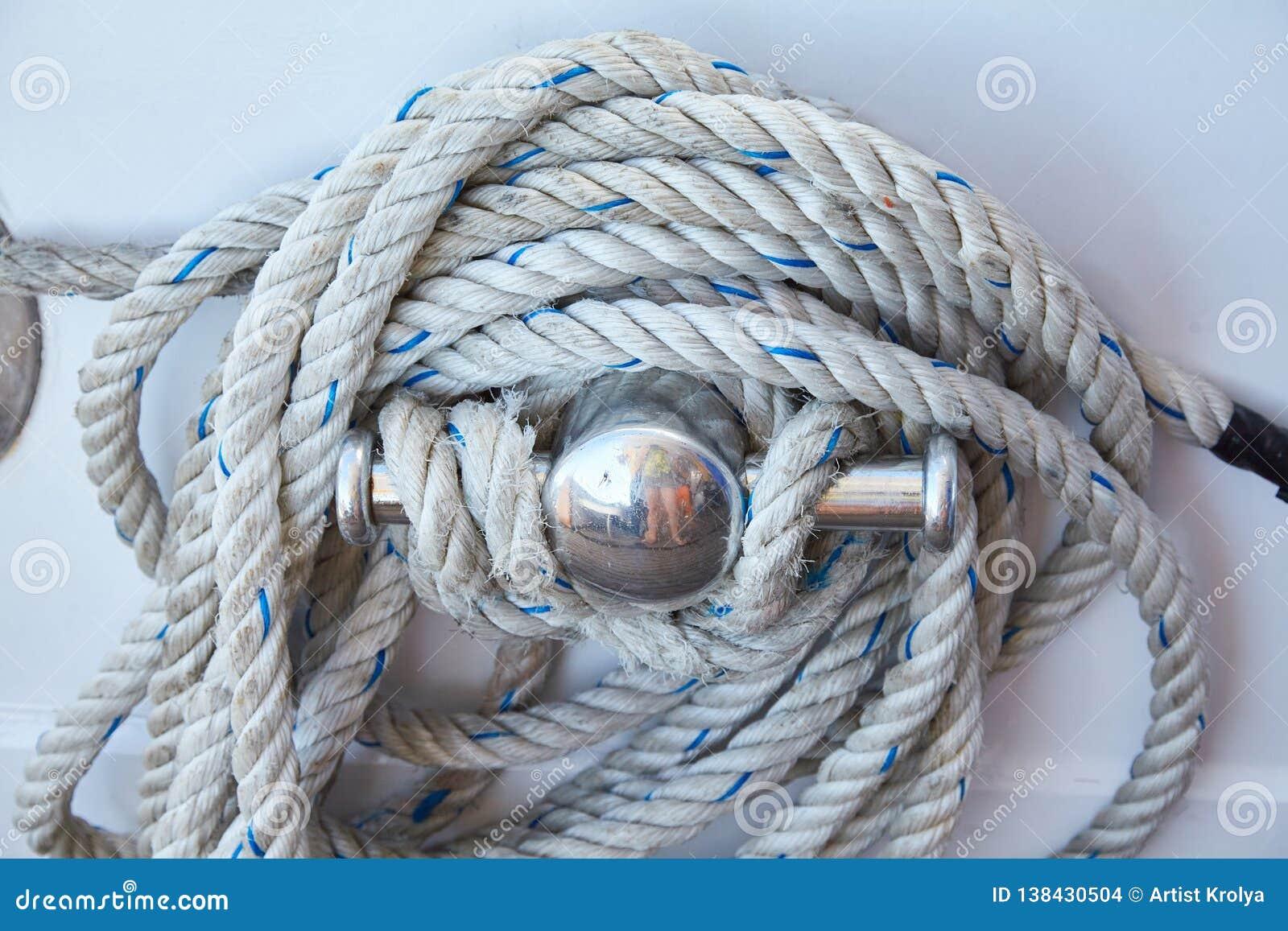 Cuerda blanca arrollada en una cubierta de barcos de madera