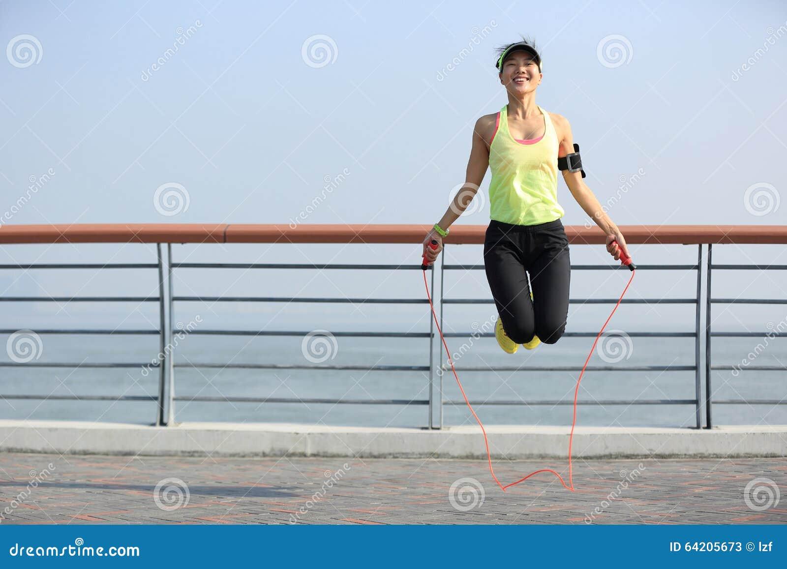 Cuerda de salto de la mujer de la aptitud en la playa