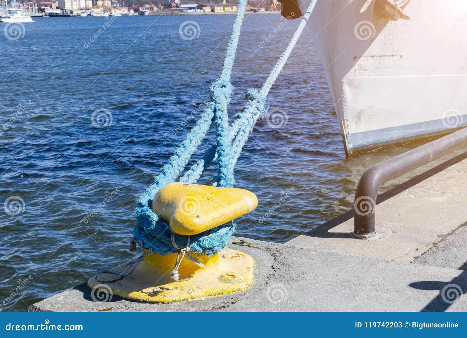 Cuerda del amarre atada al bolardo en el embarcadero Cuerda náutica de la amarradura El envío se opone concepto Cuerdas de la nav