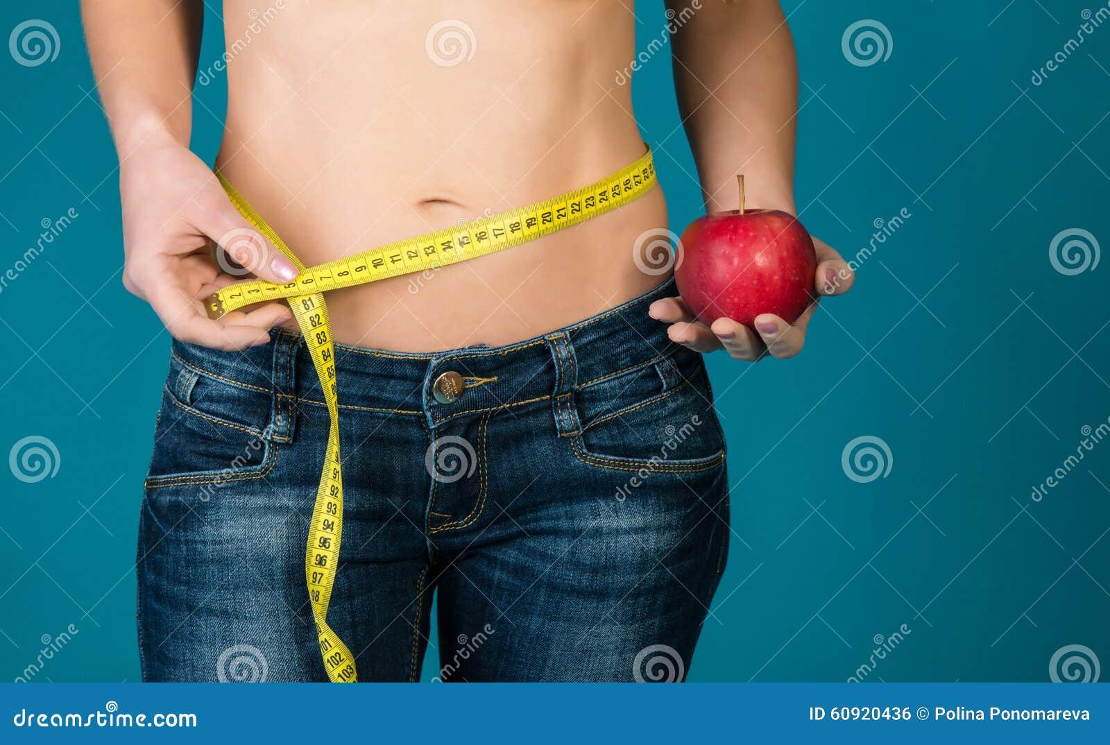 Cuerpo femenino apto con la manzana y la cinta métrica Aptitud sana y consumición de concepto de la forma de vida
