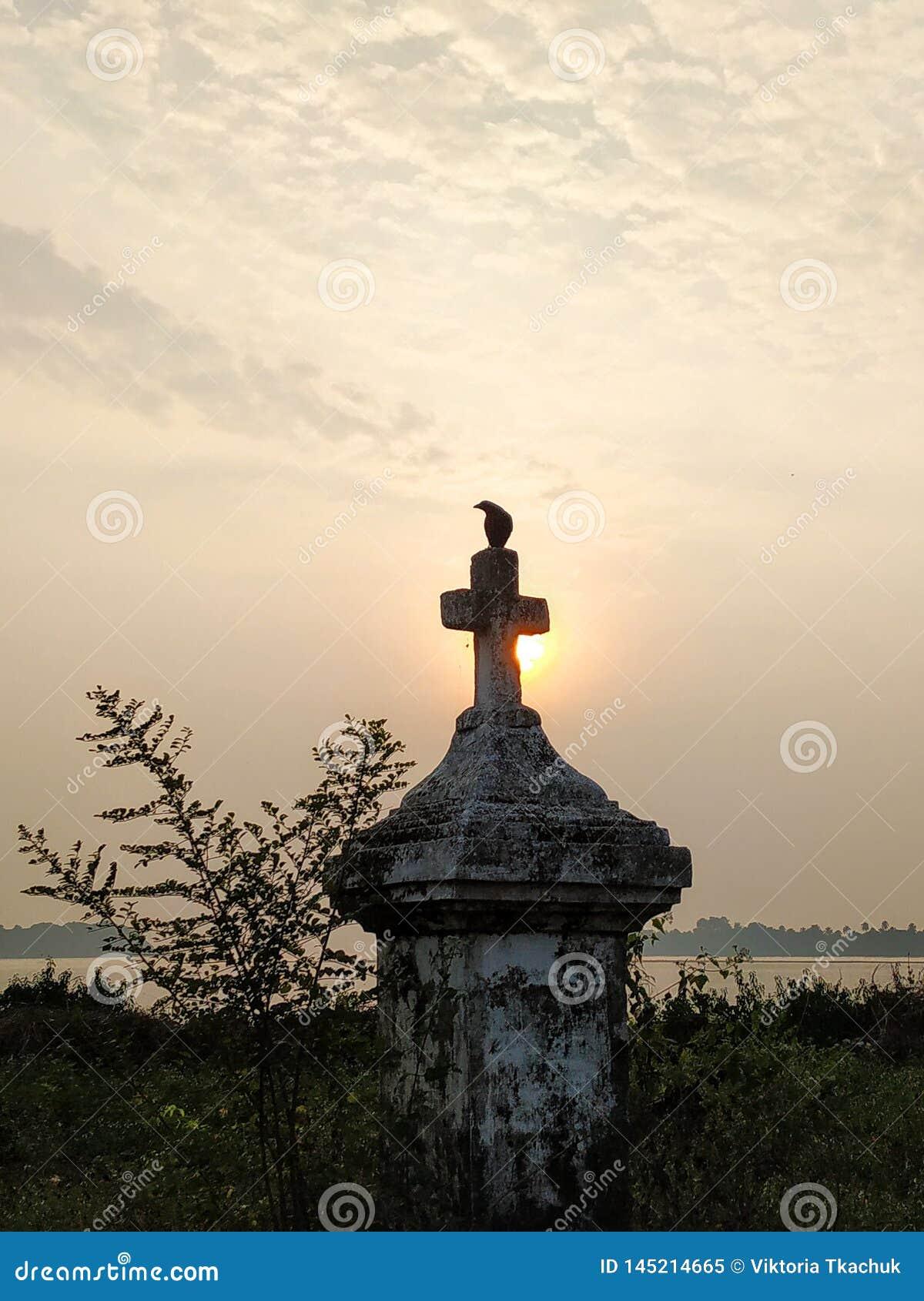 Cuervo y cruz en la puesta del sol