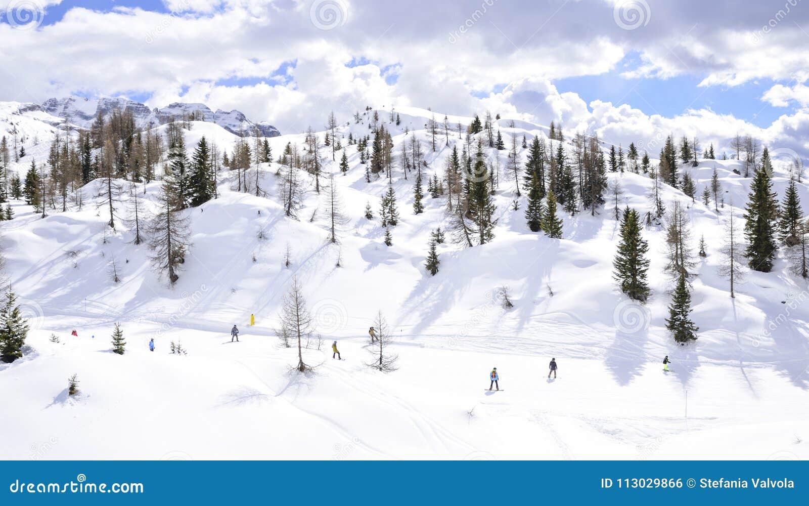 Cuesta del esquí con los esquiadores en las montañas