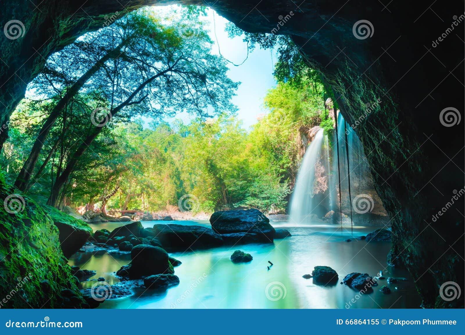 Cueva asombrosa en bosque profundo con el fondo hermoso de las cascadas en la cascada de Haew Suwat en el parque nacional de Khao