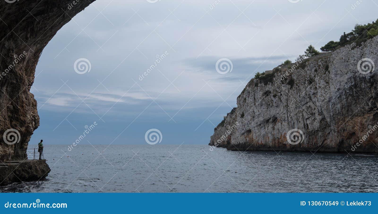 Cuevas de Zinzulusa, cerca de Castro en la península de Salento en Puglia, Italia La persona se coloca en tablón de cuadrilla en
