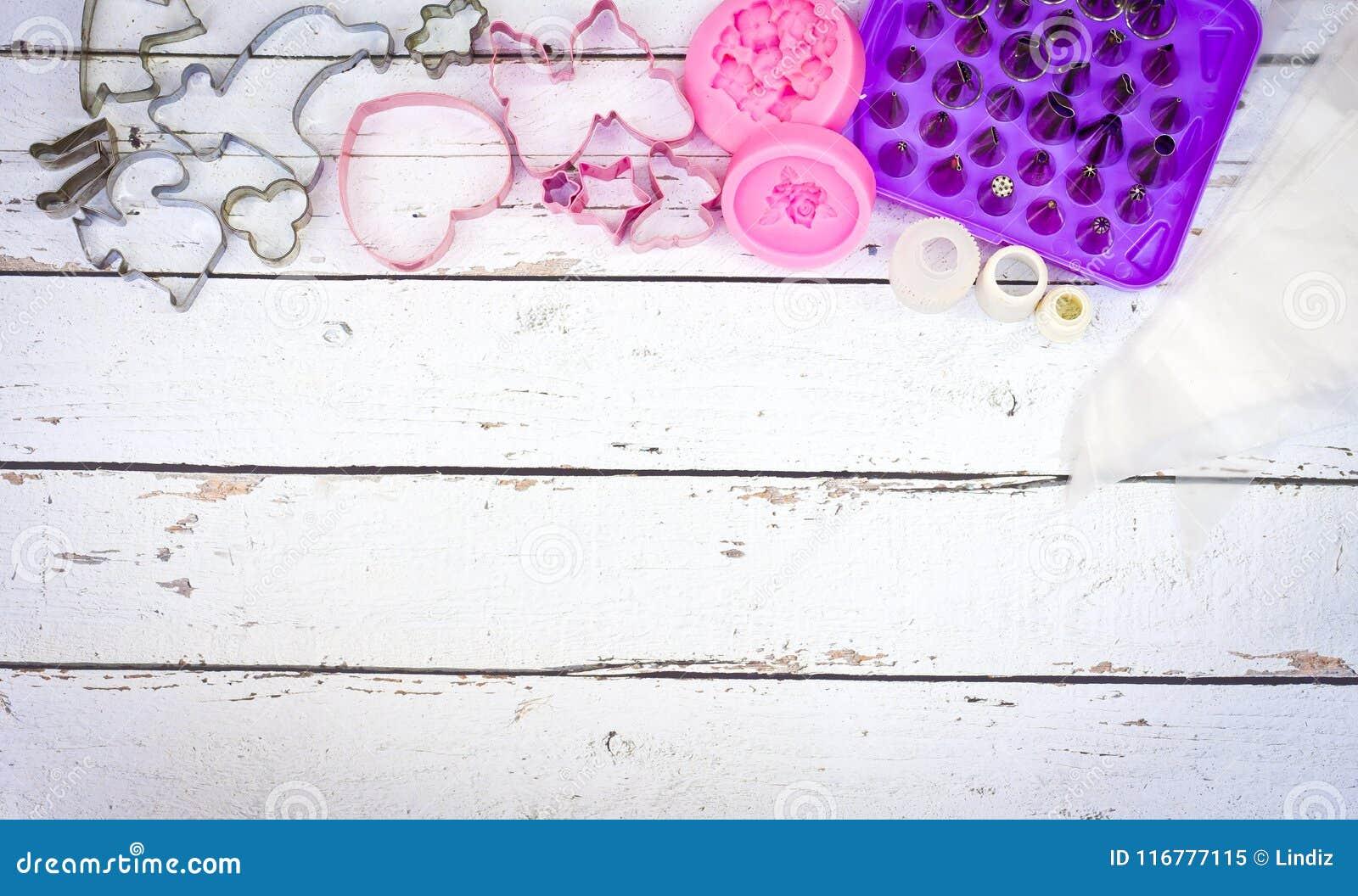Cueza las herramientas para el molde de la galleta y de la torta para el mollete y la magdalena en el fondo de madera blanco