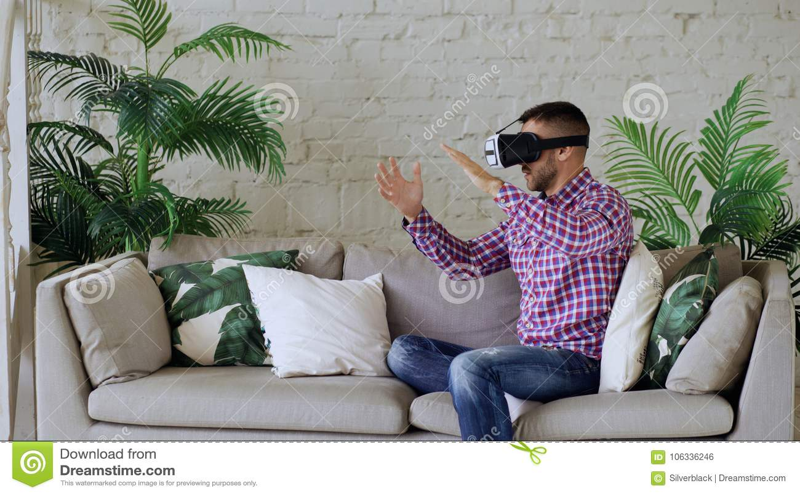 Cuffia avricolare d uso di realtà virtuale del giovane uomo allegro che ha video esperienza di 360 VR mentre sedendosi sullo stra