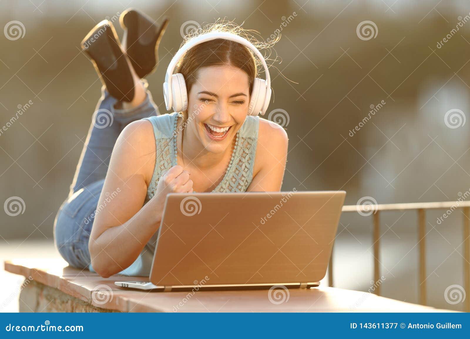 Cuffie d uso della ragazza emozionante che guardano media sul computer portatile