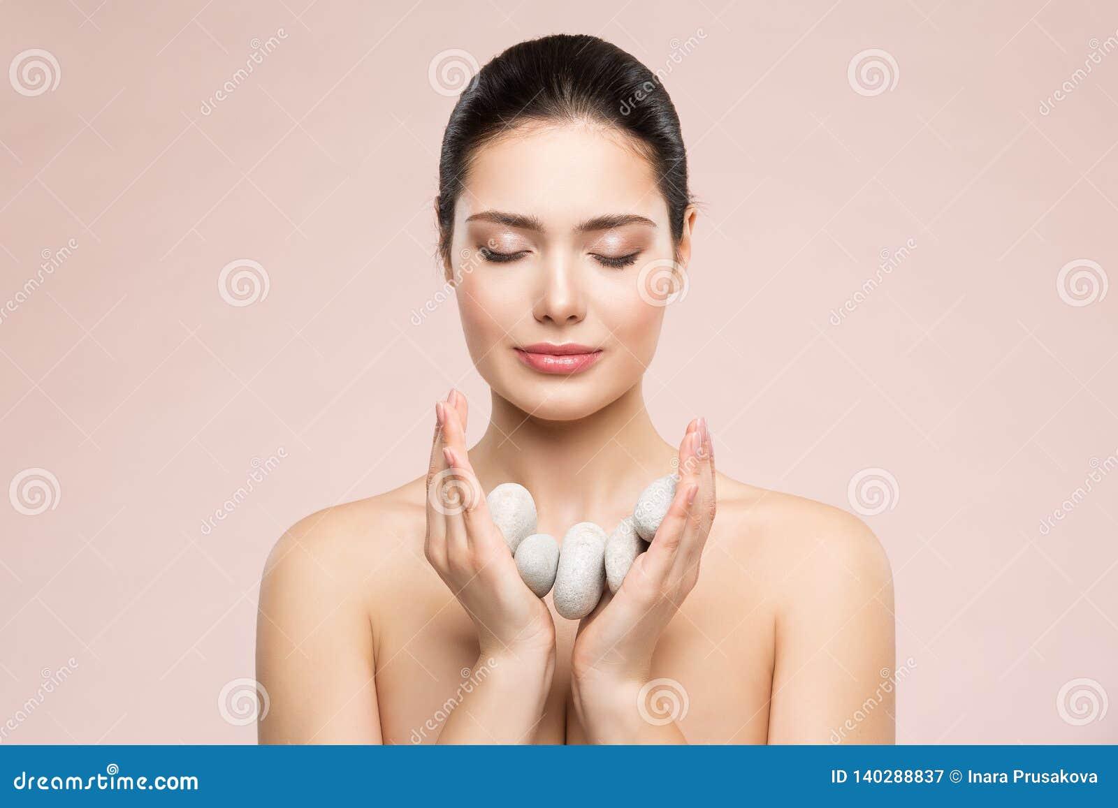 Cuidado da beleza da mulher e tratamento, modelo bonito Holding Massage Stones nas mãos, sonhos felizes da saúde da menina