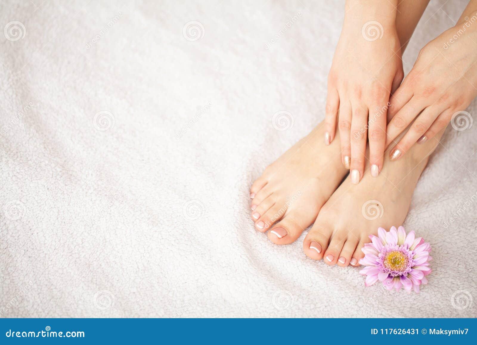 Cuidado da mão e do prego Pés e mãos bonitos do ` s das mulheres após o tratamento de mãos e o pedicure no salão de beleza Tratam