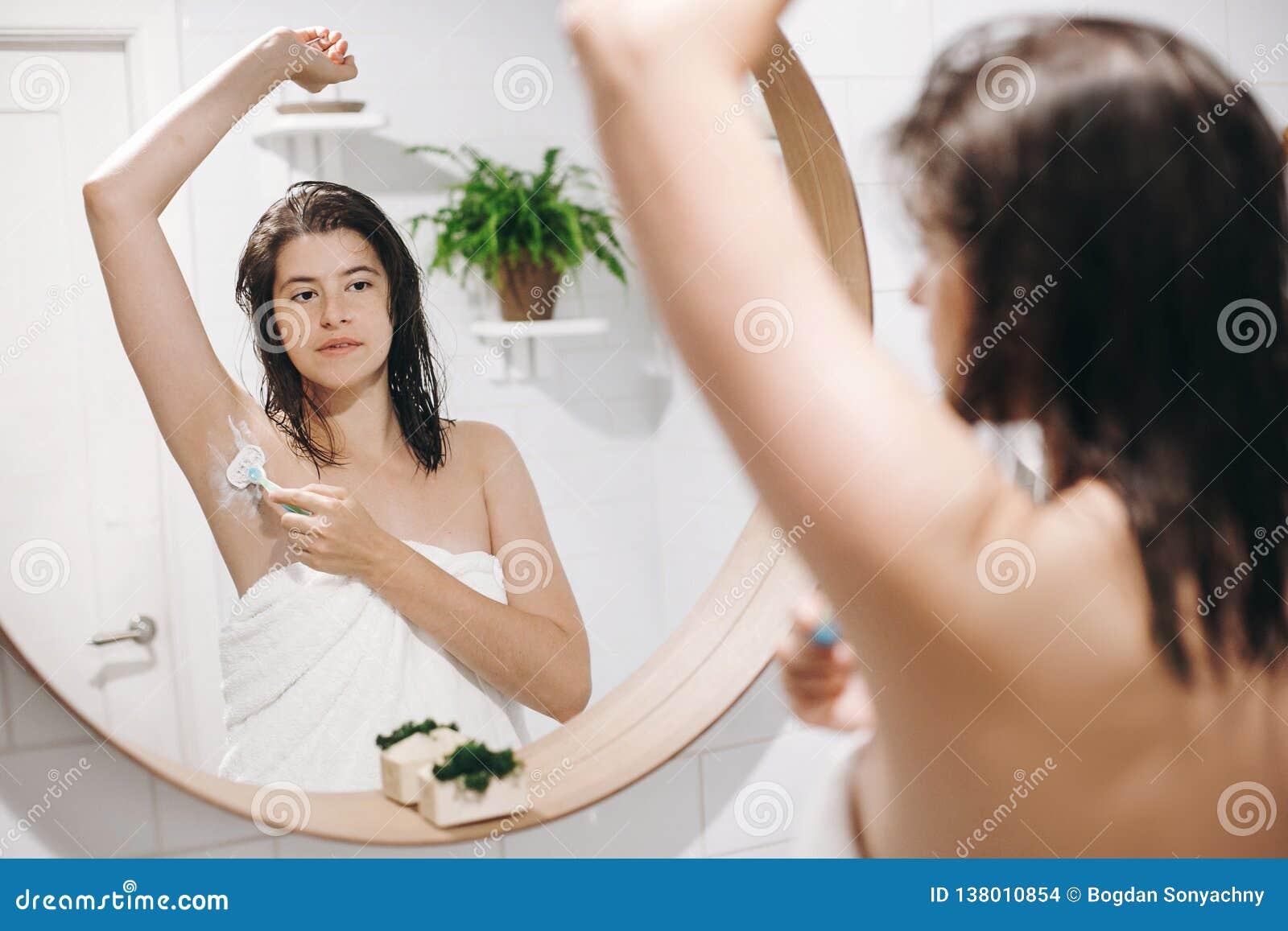 Cuidado da pele e do corpo Conceito da remoção do cabelo Mulher após o chuveiro que barbeia com lâmina Mulher atrativa nova na ra