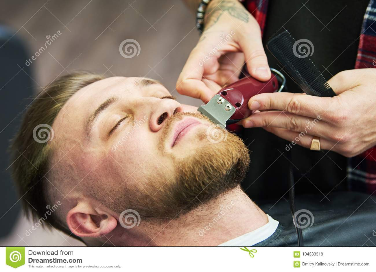 Cuidado de la barba hombre mientras que el recorte de su pelo facial cortó en la barbería