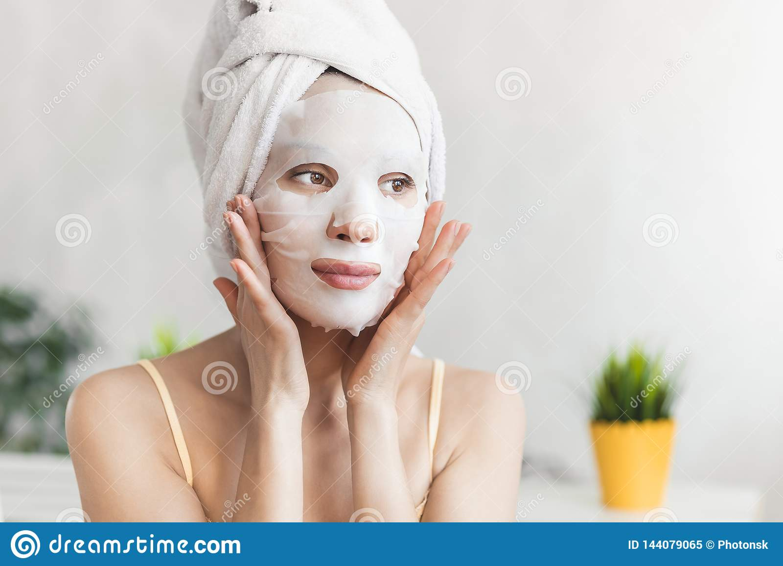 Cuidado de piel de la cara Mujer joven atractiva envuelta en toalla de baño, con la mascarilla hidratante blanca Concepto del cui