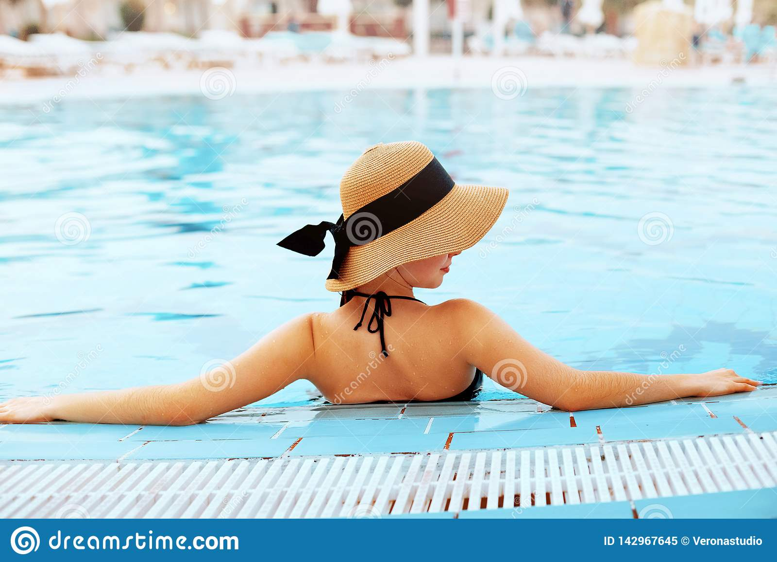 Cuidado del cuerpo de la mujer del verano Muchacha atractiva hermosa con la piel sana en el bikini rayado elegante, sombrero de S