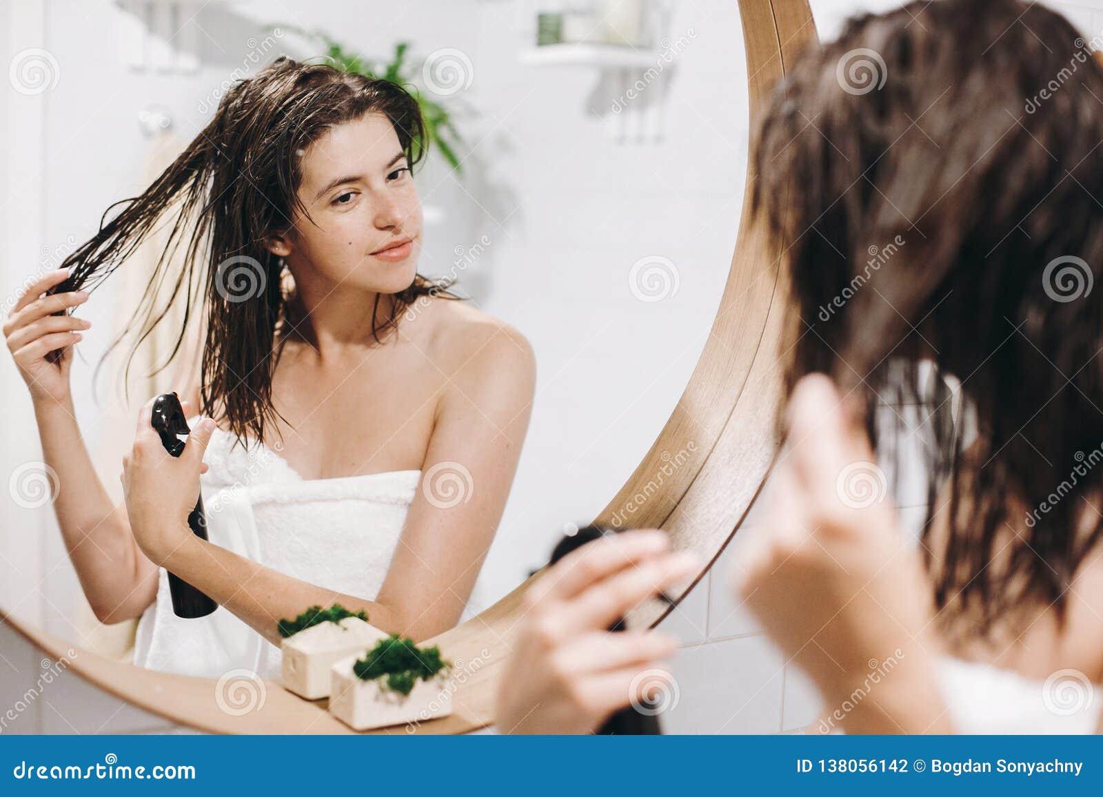 Cuidado del pelo y del cuerpo Mujer feliz joven en la toalla blanca que aplica la máscara en el pelo en cuarto de baño, reflexión