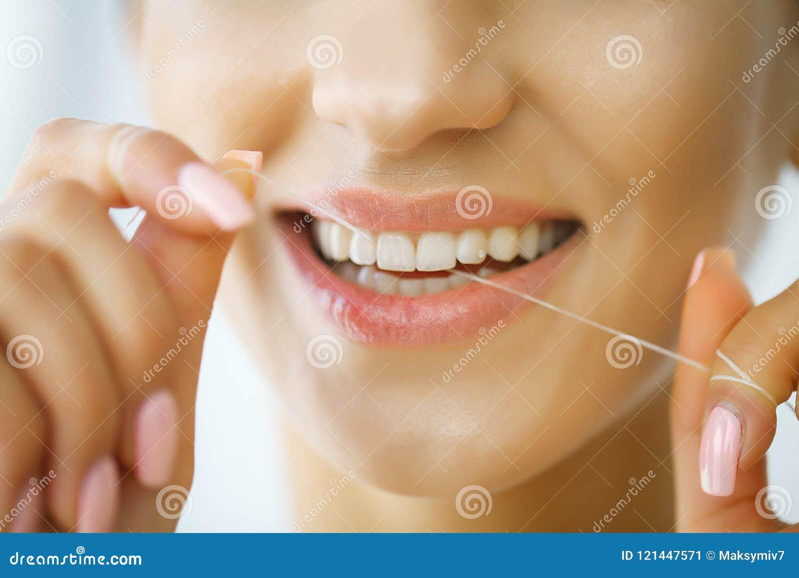 e731d09ea Cuidado dental Mulher com sorriso bonito usando o Floss para os dentes H