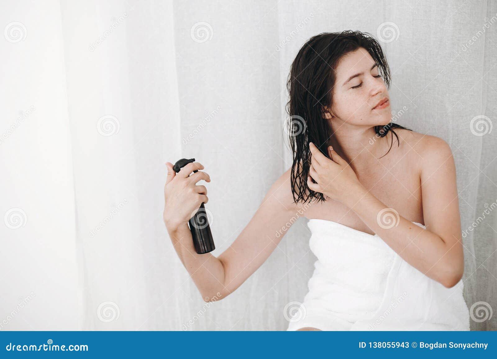 Cuidado do cabelo e do corpo Mulher feliz nova na toalha branca que aplica a máscara do condicionador no cabelo no banheiro Mulhe