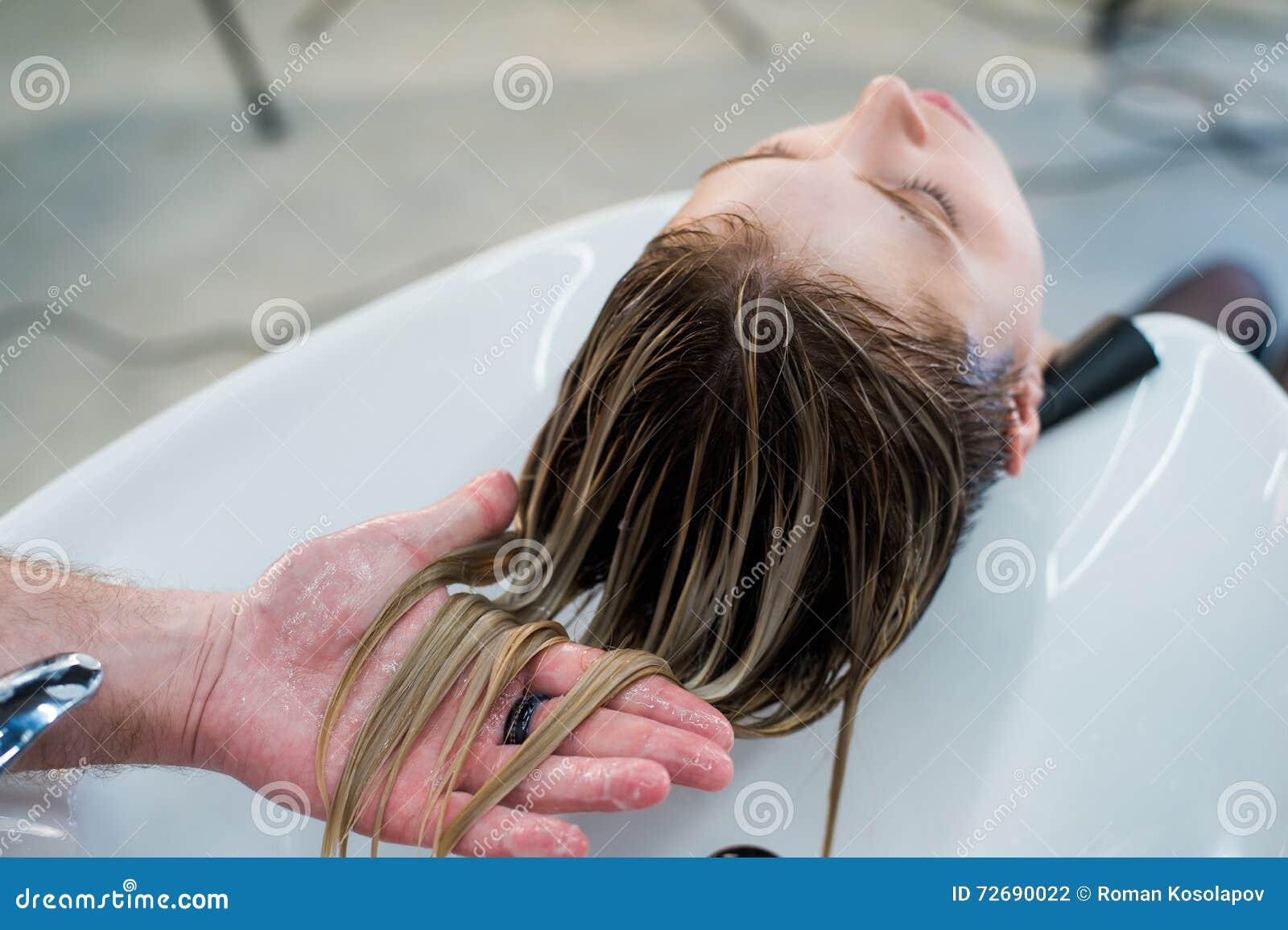 Cuidados capilares no salão de beleza moderno dos termas Cabeleireiro masculino que lava os cabelos adolescentes da menina