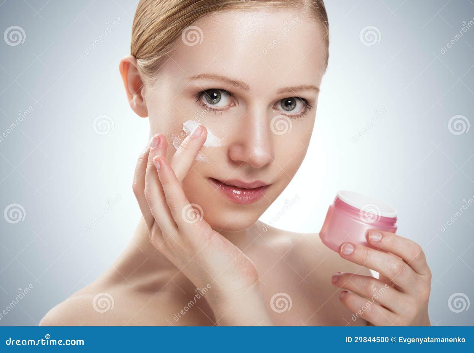 Cuidados com a pele. menina saudável da beleza feliz com o frasco do creme