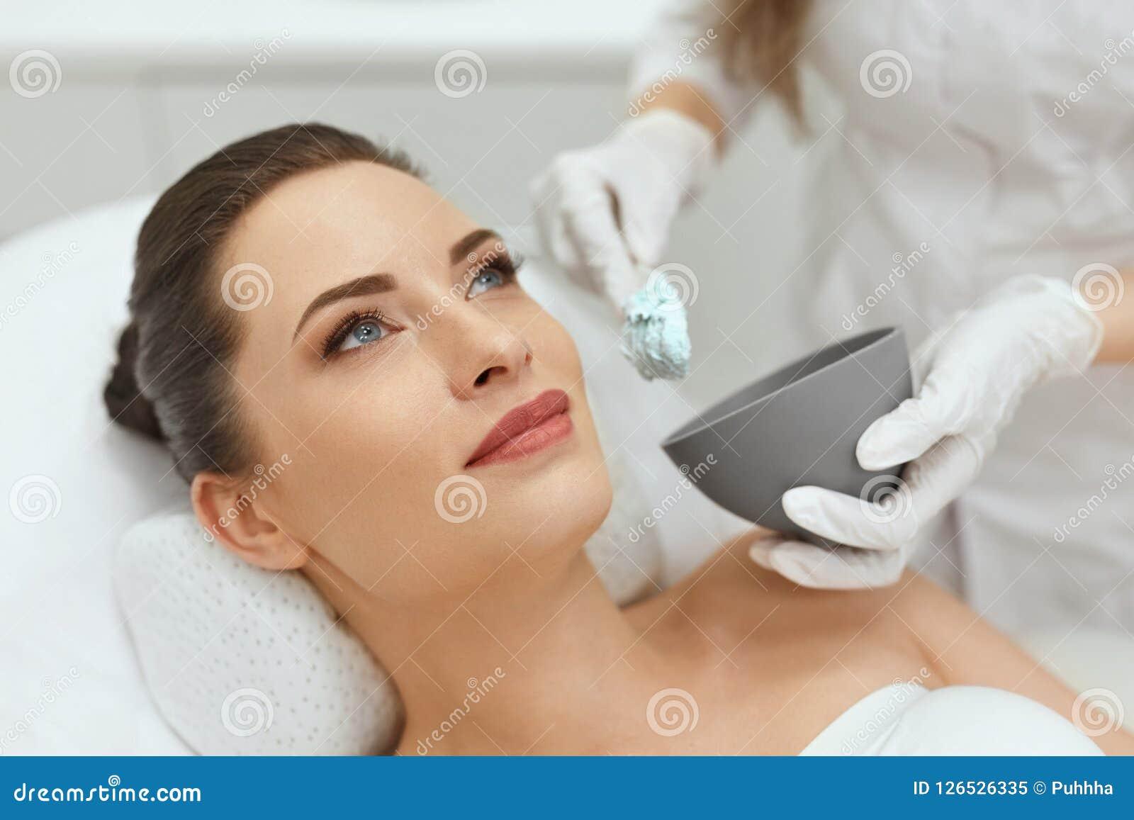 Cuidados com a pele da cara Mulher que faz a máscara facial do Alginate na cosmetologia