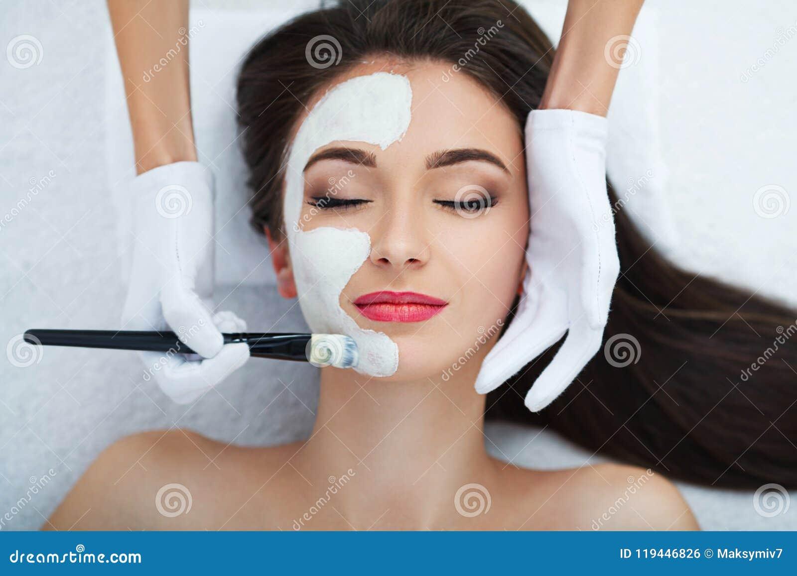 Cuidados com a pele faciais Mulher bonita que obtém a máscara cosmética no salão de beleza
