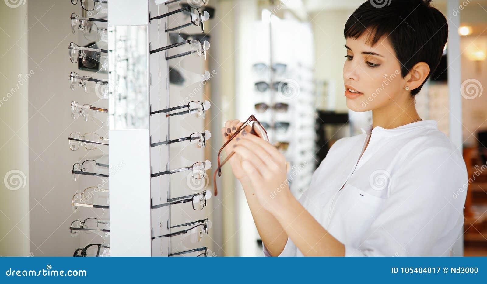 Cuidados médicos, visão e conceito da visão - mulher feliz que escolhe vidros na loja do sistema ótico