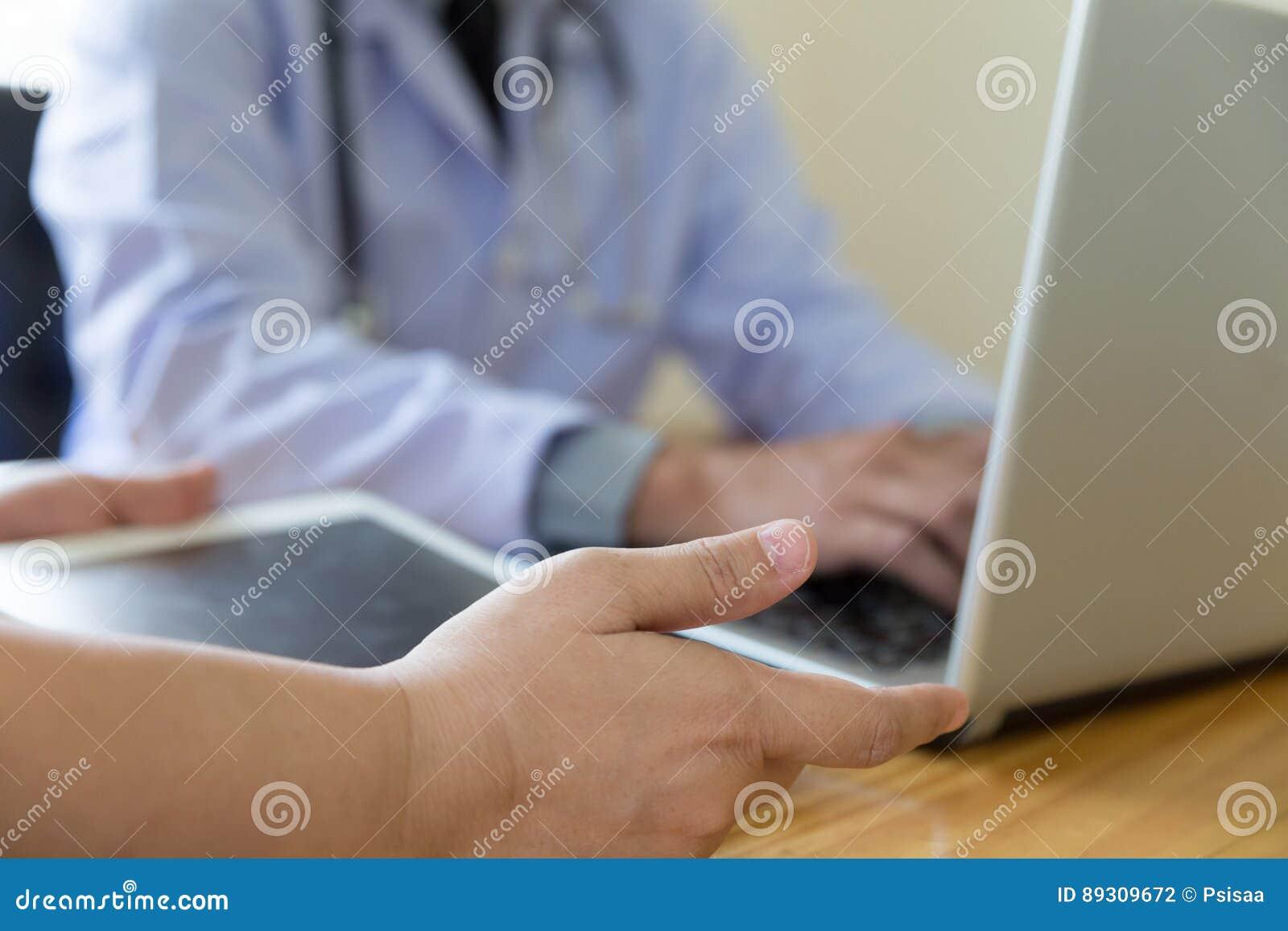 Cuide la mano que trabaja con el comput digital moderno de la tableta y del ordenador portátil