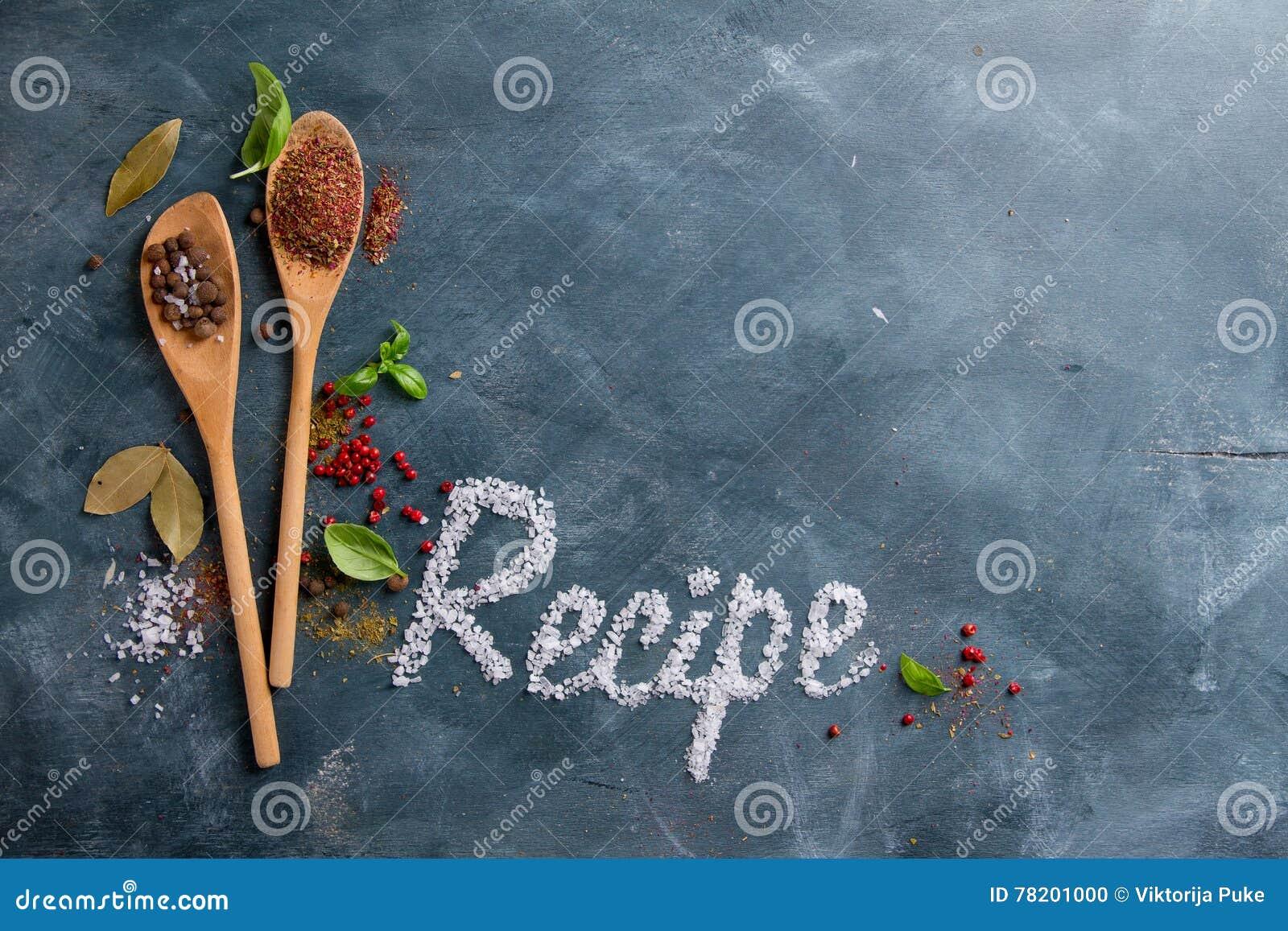 Cuillères en bois avec des épices et le mot de recette