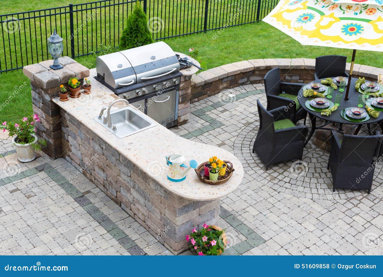 Cuisine et table de salle à manger extérieures sur un patio pavé