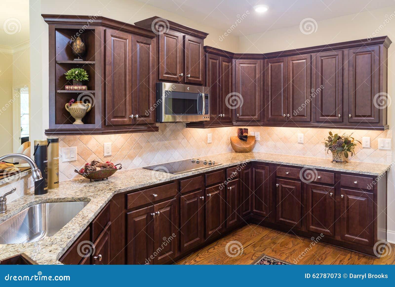 Cuisine moderne avec les cabinets fonc s et le plancher en for Cuisine plancher bois