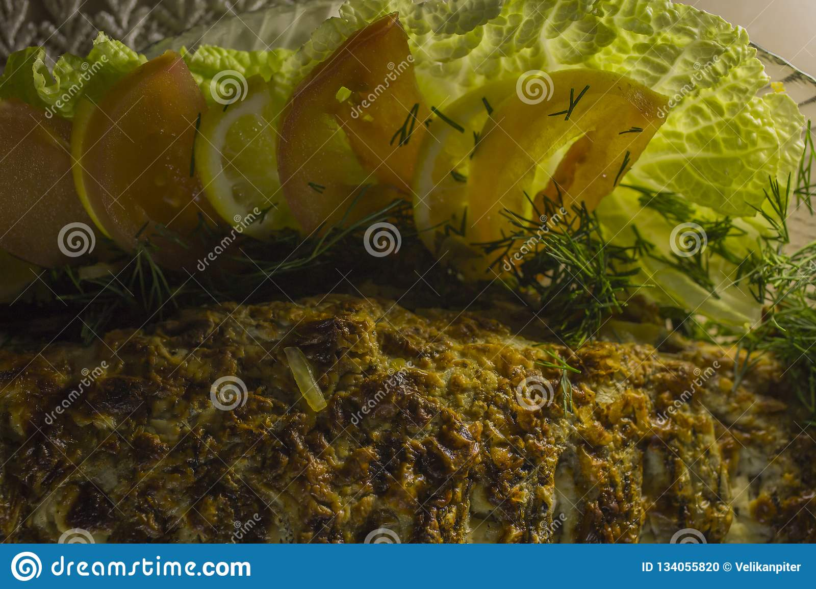 Stuffed carp, decorated with vegetables. Fish dish.