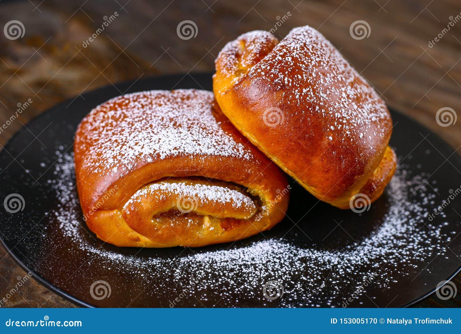 Cuisson d un plat noir Petits pains doux avec du sucre glace