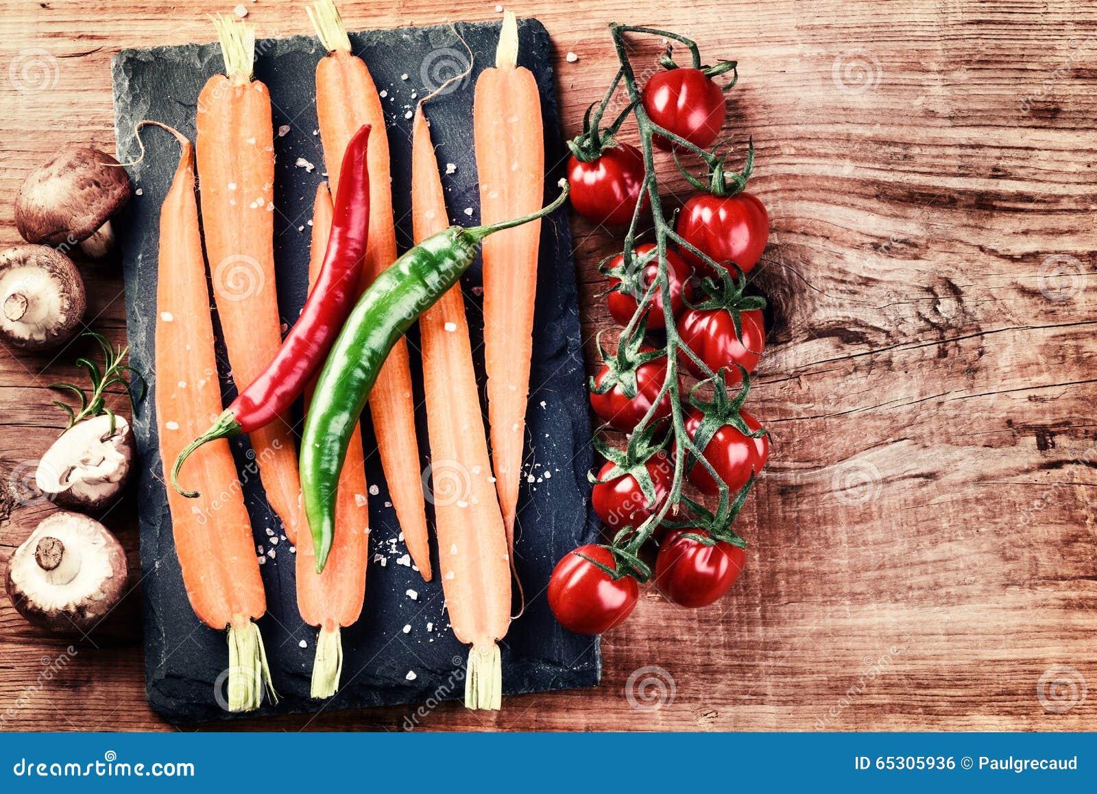 Cuisson de l arrangement avec les légumes organiques frais sur le vieux backgr en bois