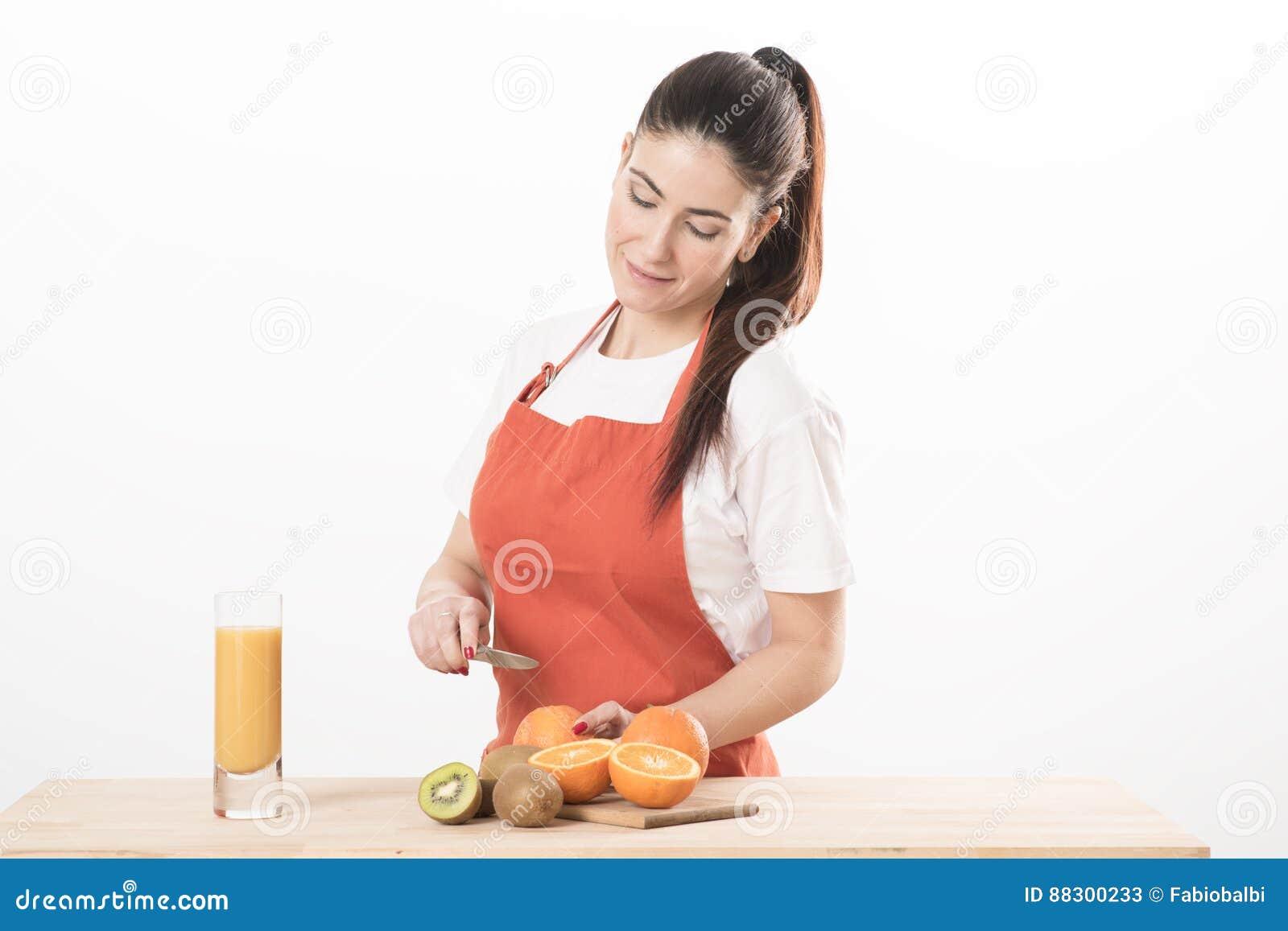Cuisson de port debout de tablier de jeune femme, coupant le fruit sur un conseil